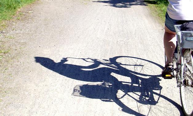 Brutalinski tritt junge Frau auf einem Fahrrad gegen den Kopf